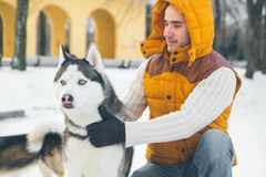 Man walking with dog winter time with snow in forest Malamute an Stock Photo