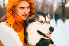 Man walking with dog winter time with snow in forest Malamute and Huskies friendship Stock Photo