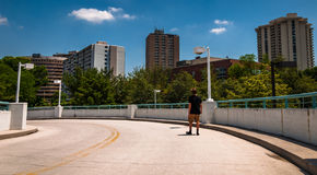 Man walking down a parking garage ramp, looking at highrises in Stock Photo