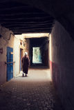 Man walking down in a shadowed alley in the medina of Essaouira, Stock Photography