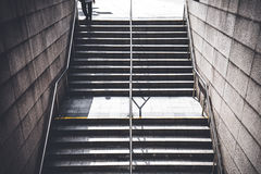 A man walking down stairs to go to underground train station. stock photos