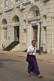 A man walking down the street in Yangon wearing traditional Burmese longyi Stock Photo