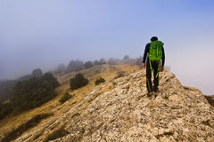 Man walking on the edge of a cliff in foggy Royalty Free Stock Photography