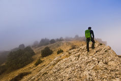 Man walking on the edge of a cliff in foggy Stock Photography