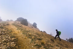 Man walking on the edge of a cliff in foggy Stock Photo