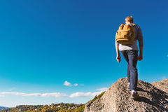 Man walking on the edge of a cliff. High above the mountains Royalty Free Stock Images