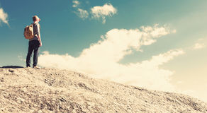 Man walking on the edge of a cliff. High above the mountains Stock Image