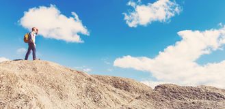 Man walking on the edge of a cliff. High above the mountains Stock Photos
