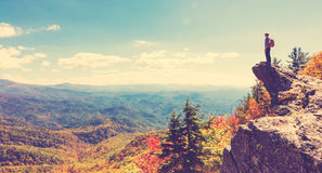 Man walking on the edge of a cliff. High above the mountains Stock Images