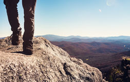 Man walking on the edge of a cliff high above the mountains. Below Royalty Free Stock Photo