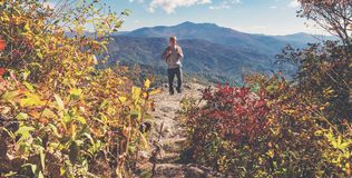 Man walking on the edge of a cliff. High above the mountains Royalty Free Stock Photo