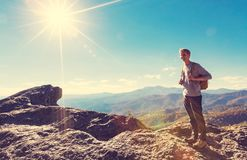 Man walking on the edge of a cliff. High above the mountains Stock Photography