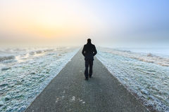Man walking on an empty desolate raod royalty free stock photo