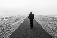 Man walking on an empty desolate raod Royalty Free Stock Image