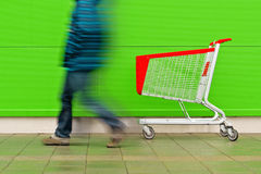 Man Walking by Empty Shopping Cart Trolley. Motion Blur Man Walking by Empty Shopping Cart Trolley in front of a Shopping Mall as Consumerism Concept Background Stock Photo