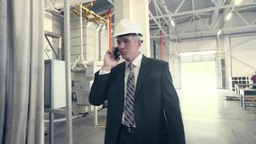 Man walking through factory and talking on phone stock video
