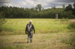 Man walking through the field to the hunters cab Royalty Free Stock Photos