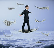 Man walking on flying dollar. Businessman walking on abstract flying dollar banknote in sky Royalty Free Stock Photos