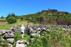 Man walking on footpath dry stone walled area Royalty Free Stock Photo