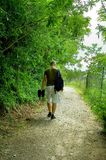 Man walking in forest. Carrying skates Royalty Free Stock Photos