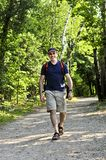 Man walking on forest trail. Happy middle aged man walking on a forest trail Royalty Free Stock Image