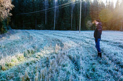 Man walking on frozen field Stock Photo