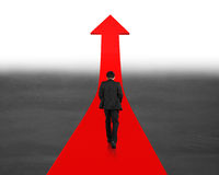 Man walking on going up red arrow Stock Images
