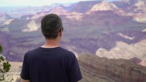 Man walking in Grand Canyon. Near cliff stock video footage