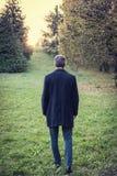 Man walking on grass meadow Stock Photo