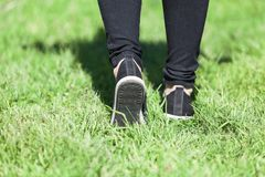Man walking on grass in sports shoes, close up rear view Royalty Free Stock Photos