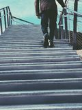 Man Walking on Gray Stairs Royalty Free Stock Images