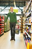 Man walking in grocery store. Mid adult man with shopping basket walking in grocery store and looking at products stock images