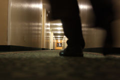 Man walking in hallway. A dark, floor-level view of a man's feet as he walks down a dimly lit hotel hallway.  Some motion blur Stock Photo