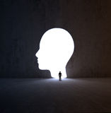 Man walking into a head-shaped opening in a wall Royalty Free Stock Image