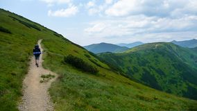 Man walking in hills on path with big bag in tatra mountains royalty free stock photo