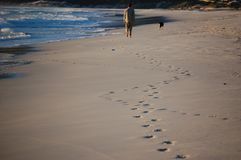 A man walking his dog along the beach near the ocean, leaving his footprints on the sand stock image
