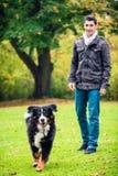 Man walking his dog in fall park. Man walking his dog in autumn park royalty free stock photo