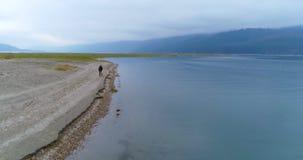 Man walking with his dog near lakeside 4k. Man walking with his dog near lakeside at countryside 4k stock video