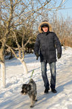 Man walking his dog in winter snow Royalty Free Stock Photo