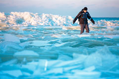 Man walking on icy beach along the Baltic sea Royalty Free Stock Photos