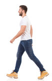 Man walking in jeans and white t-shirt Royalty Free Stock Photography