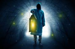 Man walking with lantern in a dark tunnel Stock Photo