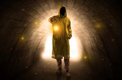 Man walking with lantern in a dark tunnel Stock Image
