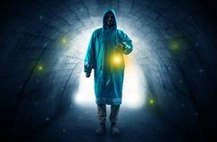 Man walking with lantern in a dark tunnel. Ugly man in raincoat walking with glowing lantern in a dark tunnel Stock Photo