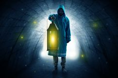 Man walking with lantern in a dark tunnel Stock Images
