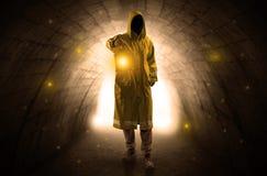 Man walking with lantern in a dark tunnel. Ugly man in raincoat walking with glowing lantern in a dark tunnel Stock Image