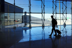 Man walking with luggage in the airport. Traveler man walking with luggage in the airport Stock Photo