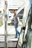 Man walking with luggage and mobile phone. Portrait of man walking with luggage and mobile phone Royalty Free Stock Image