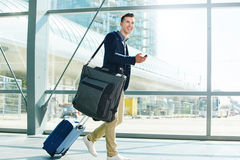 Man walking with luggage and phone in station smiling. Full body portrait of man walking with luggage and phone in station smiling Royalty Free Stock Images