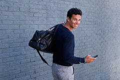 Man walking with mobile phone and bag turning and smiling. Portrait of man walking with mobile phone and bag turning and smiling Stock Image